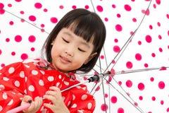 Chinesisches kleines Mädchen, das Regenschirm mit Regenmantel hält Lizenzfreie Stockfotos
