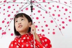 Chinesisches kleines Mädchen, das Regenschirm mit Regenmantel hält Lizenzfreies Stockfoto