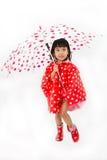 Chinesisches kleines Mädchen, das Regenschirm mit Regenmantel hält Lizenzfreie Stockfotografie
