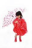 Chinesisches kleines Mädchen, das Regenschirm mit Regenmantel hält Stockfotografie