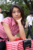 Chinesisches Mädchen, das auf Freund mit Koffer wartet lizenzfreie stockfotografie