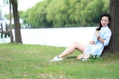 Chinesisches Mädchen, das ein Buch unter Baum liest Blonde schöne junge Frau mit Buch sitzen auf dem Gras Stockbild