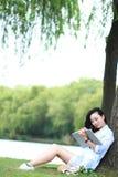 Chinesisches Mädchen, das ein Buch unter Baum liest Blonde schöne junge Frau mit Buch sitzen auf dem Gras Stockfotos