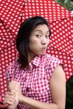 Chinesisches Mädchen, das ein Gesicht mit punktiertem Regenschirm bildet stockbilder