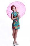 Chinesisches Mädchen, das einen cheongsam Regenschirm trägt Stockfotografie