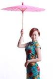 Chinesisches Mädchen, das einen cheongsam Regenschirm trägt Stockfotos