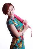 Chinesisches Mädchen, das einen cheongsam Regenschirm trägt Lizenzfreie Stockbilder