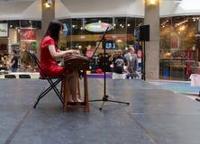 Chinesisches Mädchen, das Zither im Mall spielt Stockbilder