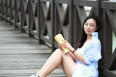 Chinesisches Mädchenlesebuch Blonde schöne junge Frau mit Buch sitzen aus den Grund Lizenzfreie Stockfotos