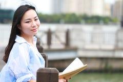 Chinesisches Mädchenlesebuch Blonde schöne junge Frau mit Buchstand nahe Zaun Lizenzfreies Stockbild