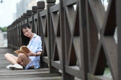 Chinesisches Mädchenlesebuch Blonde schöne junge Frau mit Buchstand nahe Zaun Lizenzfreie Stockbilder