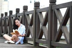 Chinesisches Mädchenlesebuch Blonde schöne junge Frau mit Buchstand nahe Zaun Stockfotografie