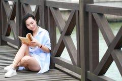Chinesisches Mädchenlesebuch Blonde schöne junge Frau mit Buchstand nahe Zaun Lizenzfreie Stockfotografie