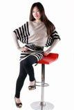 Chinesisches Mode-Modell, das einen Stuhl sitzt Lizenzfreies Stockbild
