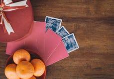 Chinesisches Neujahrsfest - Mandarine, Teeschale und rotes Paket mit chinesischem Geld auf Holztisch lizenzfreie stockbilder