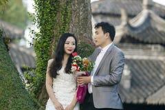 Chinesisches Paarhochzeit portraint vor alten Bäumen und Altbau Lizenzfreie Stockbilder