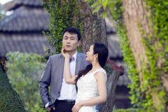 Chinesisches Paarhochzeit portraint vor alten Bäumen und Altbau Lizenzfreies Stockbild