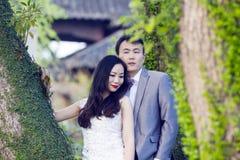 Chinesisches Paarhochzeit portraint vor alten Bäumen und Altbau Lizenzfreies Stockfoto