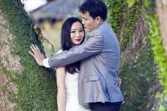 Chinesisches Paarhochzeit portraint vor alten Bäumen und Altbau Stockfoto