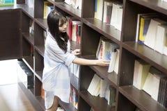 Chinesisches Porträt der jungen Schönheit erreichend für ein Bibliotheksbuch in der Buchhandlung Stockfotos