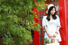 Chinesisches Porträt der jungen Schönheit nahe der alten Telefonzelle Lizenzfreie Stockbilder