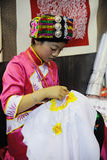 Chinesisches qiang Mädchen, das eine Abbildung stickt lizenzfreie stockfotografie