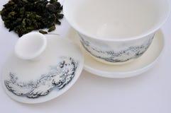Chinesisches schnitzendes Teecup und rohes Teeblatt Lizenzfreie Stockbilder