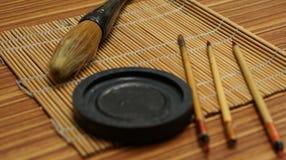 Chinesisches Schreiben auf Bürstenmatte stockfotos