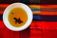 Chinesisches Teecup auf rotem Gewebe Stockfotografie