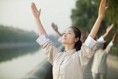 Chinesisches Volk, das Tai Ji, Arme angehoben, draußen übt Stockfoto
