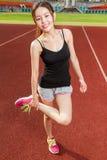 Chinesisches weibliches athelete, das Beine auf dem Sportfeld, wärmend ausdehnt Stockbilder