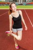 Chinesisches weibliches athelete, das Beine auf dem Sportfeld, wärmend ausdehnt Stockbild