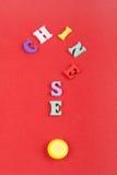 CHINESISCHES Wort auf dem roten Hintergrund verfasst von den hölzernen Buchstaben des bunten ABC-Alphabetblockes, Kopienraum für  Stockfoto