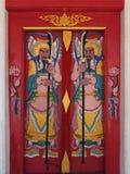 Chiness gudmålarfärg på röd dörr Royaltyfria Bilder