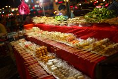 Chinesse street food on stick bar at night city streets stock photography