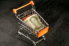 Chiniese leader Mao face in shopping cart with a paper banknote of One Chinese Yuan Stock Image