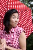 Chino hermoso con el paraguas y una mirada curiosa imagen de archivo