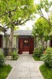 Chinois asiatique, bâtiments antiques, cours, arme à feu blanche, tuiles grises, portes et fenêtres rouges, arbres et fleurs Photo stock