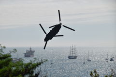 Chinook at the Bournemouth airshow 2015. A chinook silhouetted against the sky doing an aerial display at the Bournemouth airshow with ships in the   background Stock Images