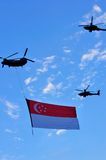 Chinook flying Singapore flag during NDP Royalty Free Stock Photos