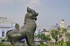 独特的Chinthe雕象在有美丽的殖民地大厦的班都拉庭院在背景中 免版税库存图片