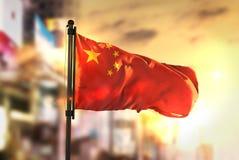 Chiny flaga Przeciw miasta Zamazanemu tłu Przy wschodu słońca Backlight zdjęcia royalty free