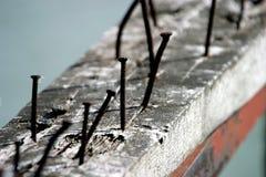 Chiodi arrugginiti che sporgono da un bordo di legno anziano fotografie stock libere da diritti