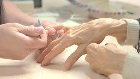 Chiodi della limatura del manicure alla donna senior stock footage