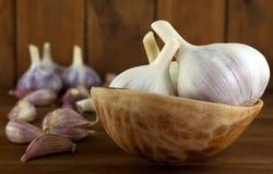 Chiodi di garofano di aglio e lampadina dell'aglio in ciotola di legno d'annata Immagine Stock Libera da Diritti