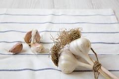 Chiodi di garofano di aglio, lampadine dell'aglio sul panno sopra superficie di legno bianca fotografie stock