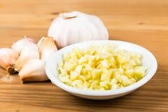 Chiodi di garofano di aglio sbucciati ed affettati con l'intera lampadina dell'aglio e chiodi di garofano come fondo Immagini Stock