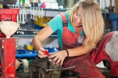 Chiodi di lucidatura della giovane donna in un negozio del meccanico Immagini Stock Libere da Diritti