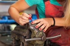 Chiodi di lucidatura della giovane donna in un negozio del meccanico Fotografia Stock Libera da Diritti