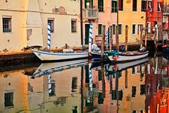 Chioggia, Venice, Italy: waterway in the old town. Chioggia, Venice, Italy - September 8, 2017: waterway in the old town with colored houses, mirror on the water royalty free stock photo
